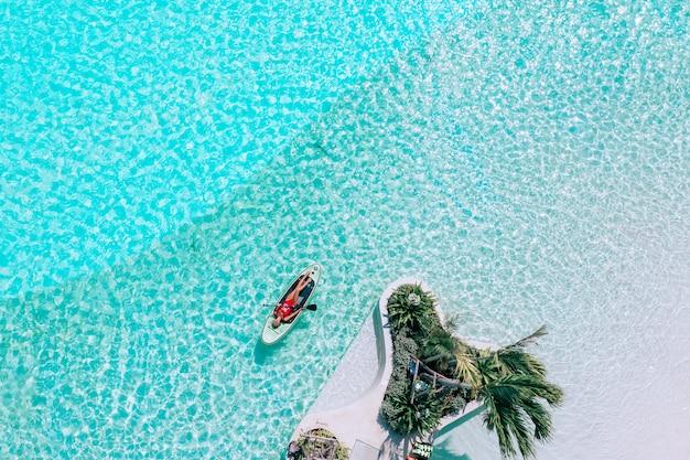 Vista aérea de uma mulher em uma placa de remo nas águas turquesas perto de palmeira