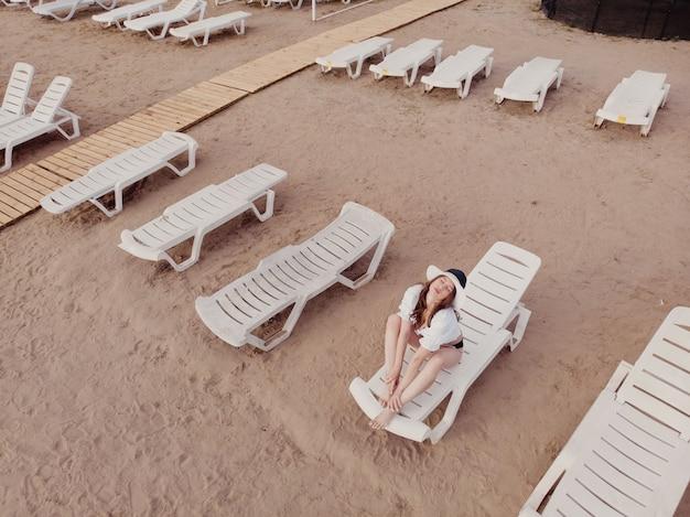 Vista aérea de uma mulher magra tomando banho de sol deitada em uma cadeira de praia