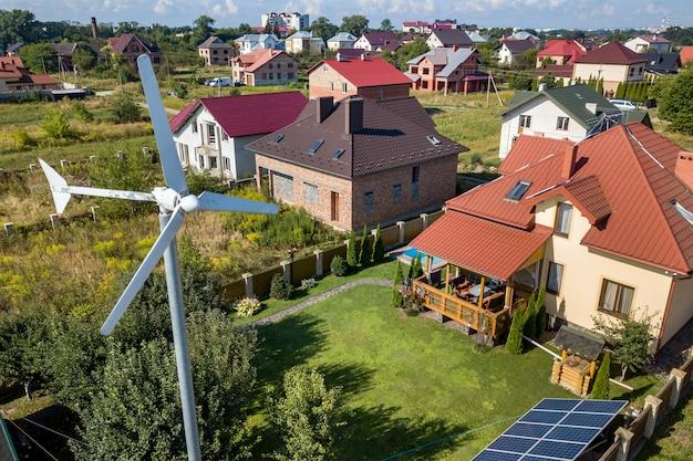 Vista aérea de uma nova casa autônoma com painéis solares, radiadores para aquecimento de água no telhado e turbina eólica no quintal verde.