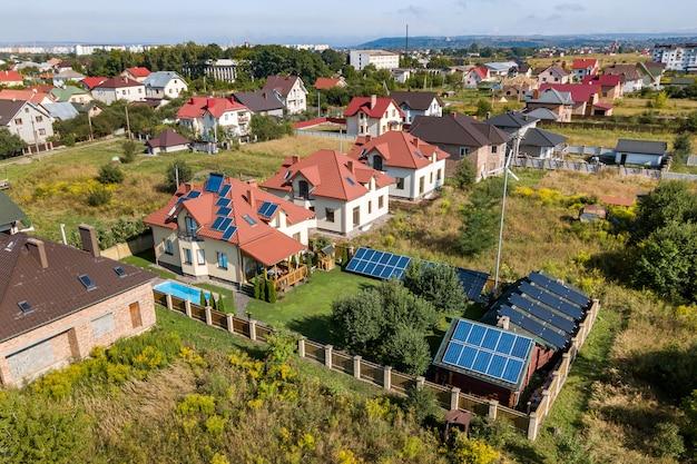 Vista aérea de uma nova casa autônoma com painéis solares, radiadores para aquecimento de água no telhado, turbina eólica e quintal verde com piscina azul.