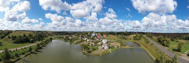 Vista aérea de uma paisagem de bela vila em uma colina perto do lago. no centro da aldeia, em uma colina, há uma bela igreja antiga. nuvens lindas, místicas e fascinantes fluem sobre a vila