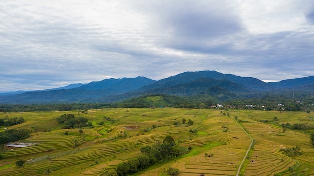 Vista aérea de uma pequena vila com cadeias de montanhas e vastos campos de arroz