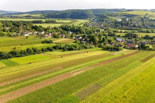 Vista aérea de uma pequena vila com muitas casas e campos agrícolas verdes