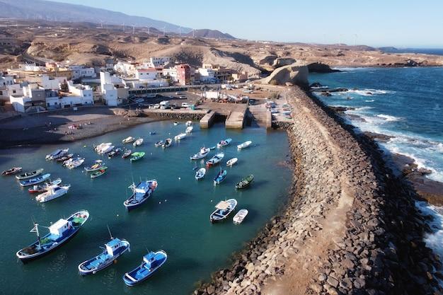 Vista aérea de uma pequena vila de pescadores com alguns barcos coloridos em tajao, tenerife, ilhas canárias.