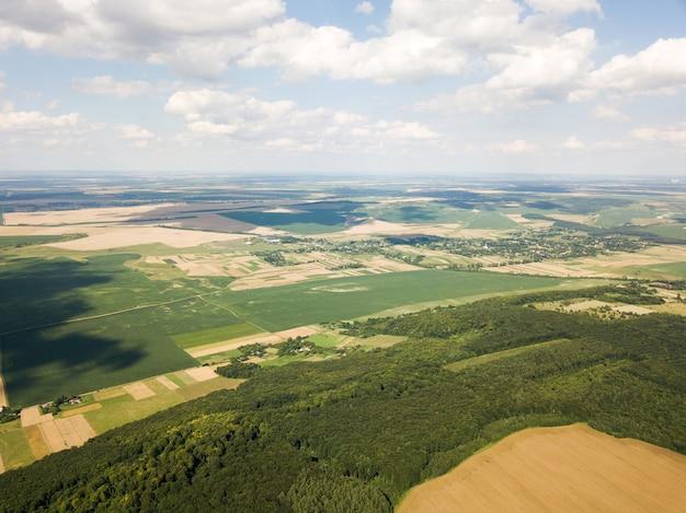 Vista aérea de uma pequena vila entre florestas e campos