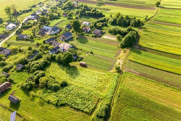 Vista aérea de uma pequena vila ganhar muitas casas e campos agrícolas verdes na primavera com vegetação fresca após a estação de semeadura em um dia quente e ensolarado.