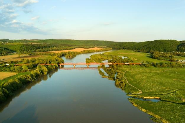 Vista aérea de uma ponte de estrada estreita que se estende ao longo de um rio lamacento na área rural verde.