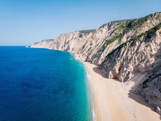 Vista aérea de uma praia de areia branca limpa, nas margens de um lindo mar azul-turquesa. grécia.
