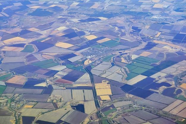 Vista aérea de uma região densamente povoada com campos multicoloridos e assentamentos