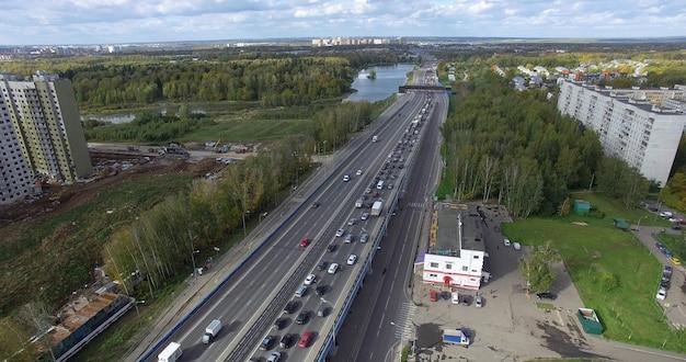 Vista aérea de uma rodovia sem fim com trânsito intenso em meio a um cenário urbano verde