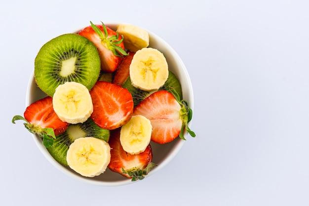 Vista aérea de uma salada de frutas cortada em uma tigela branca em branco