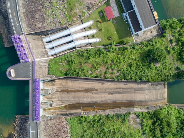Vista aérea de uma usina hidrelétrica, porta de barreira hidráulica topview e com encanamento, barragem de concreto downstream slope.