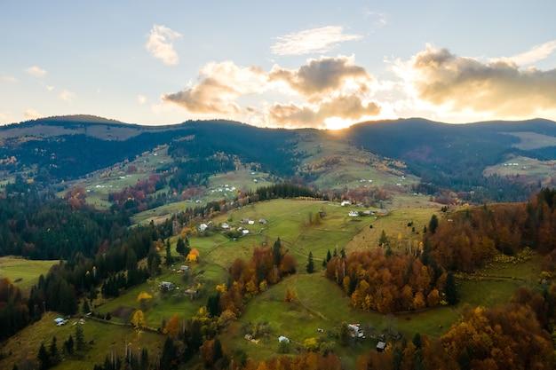 Vista aérea de uma vila distante com pequenas casas de pastor em prados de ampla colina entre árvores da floresta de outono nas montanhas dos cárpatos ucranianos ao pôr do sol.