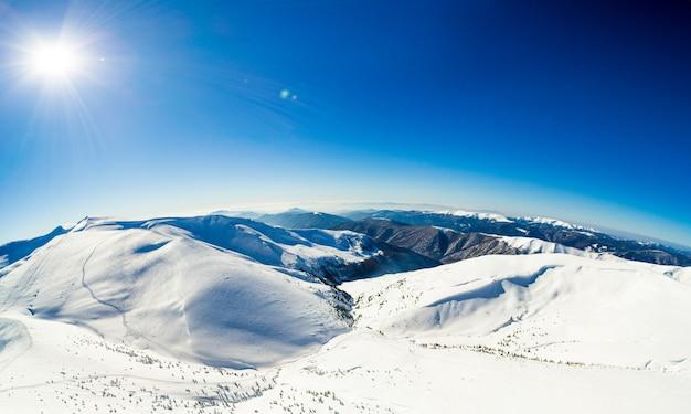 Vista aérea de uma vista incrível e hipnotizante de uma paisagem montanhosa de inverno em um dia ensolarado e gelado em uma estação de esqui