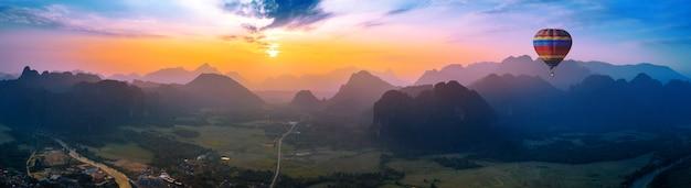 Vista aérea de vang vieng com montanhas e balão ao pôr do sol.