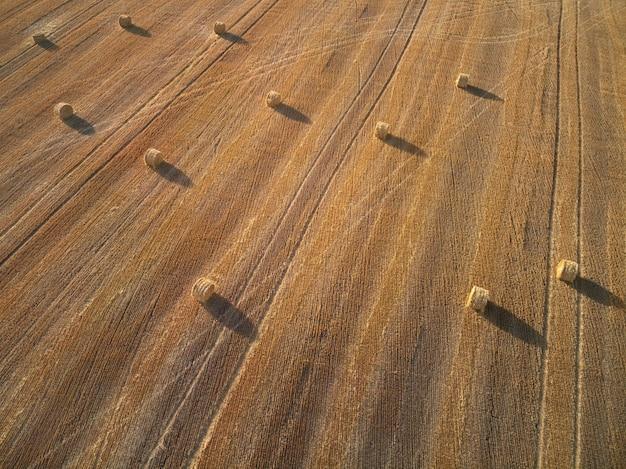 Vista aérea de vários fardos redondos de palha no campo