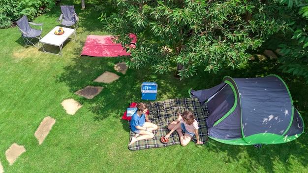 Vista aérea do acampamento de cima, mãe e filha se divertindo, barraca e equipamento de acampamento sob a árvore, conceito de férias em família no acampamento ao ar livre