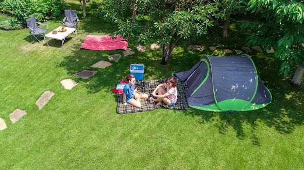 Vista aérea do acampamento de cima, mãe e filha se divertindo com a barraca e o equipamento de acampamento sob a árvore de férias familiares no conceito de acampamento ao ar livre