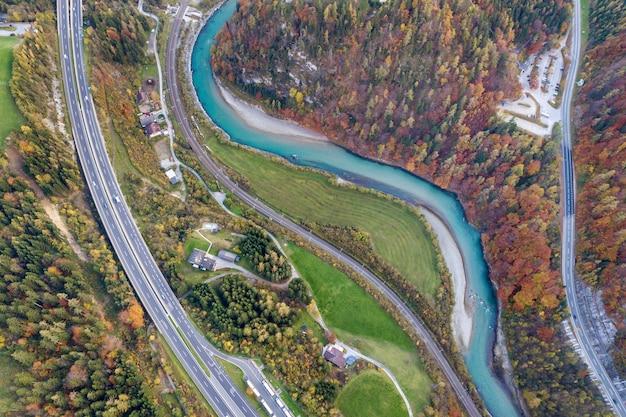 Vista aérea do amanhecer superior da estrada de velocidade da estrada entre árvores de floresta de outono amarelo e rio azul.