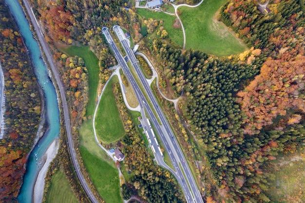 Vista aérea do amanhecer superior da estrada de velocidade da estrada que sai do túnel subterrâneo entre árvores de floresta amarelas do outono e o rio azul.