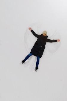 Vista aérea do anjo da neve feita por uma jovem na neve. vista do topo.