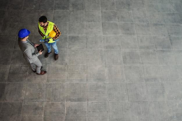 Vista aérea do arquiteto e do trabalhador da construção civil em pé no local e discutindo sobre o projeto