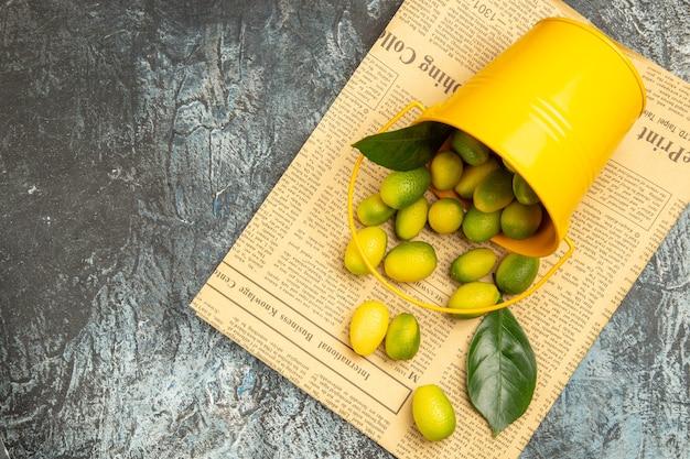 Vista aérea do balde amarelo caído com kumquats frescos nos jornais do lado esquerdo da mesa cinza