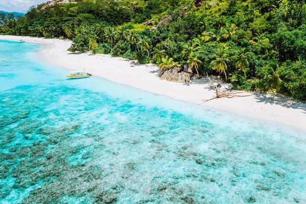 Vista aérea do barco atracado na lagoa azul de uma ilha inabitável. seychelles