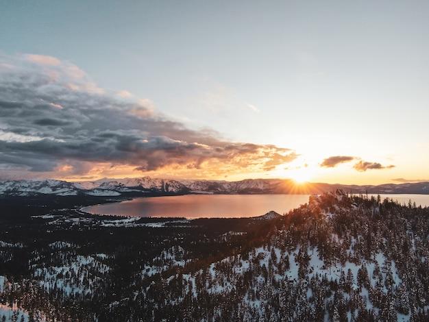 Vista aérea do belo lago tahoe capturada em um pôr do sol nevado na califórnia, eua
