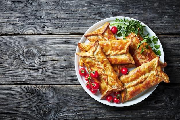 Vista aérea do borek de massa folhada recheada de frango, tortas de frango assadas, pacotes de massa folhada de frango em um prato branco com tomate cereja e salsa, visualização horizontal de cima, cópia espaço, flatlay