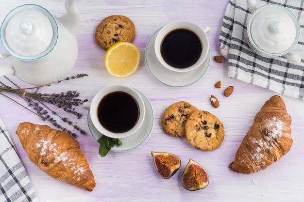 Vista aérea do bule; biscoitos; café; croissant; fig; e limão na mesa