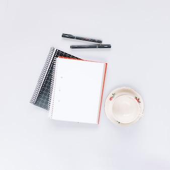 Vista aérea do caderno espiral dois; caneta e copo vazio no fundo branco