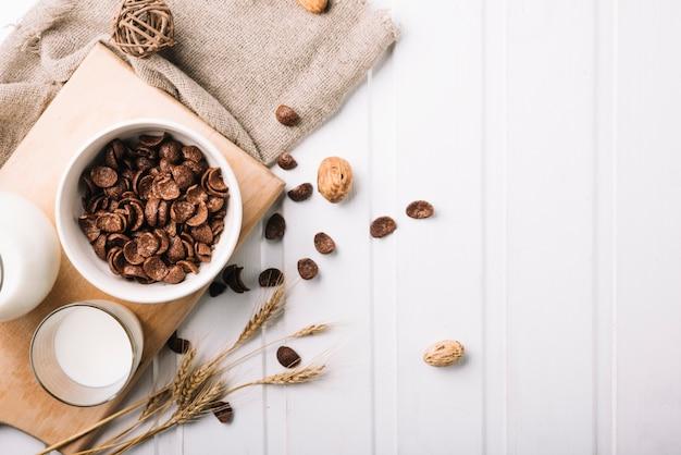 Vista aérea do café da manhã com cereais de chocolate e leite na mesa