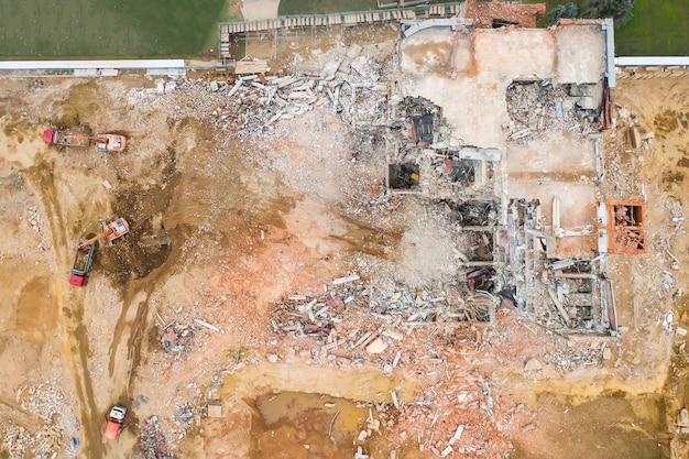 Vista aérea do canteiro de obras com prédio industrial destruído e escavadeiras.