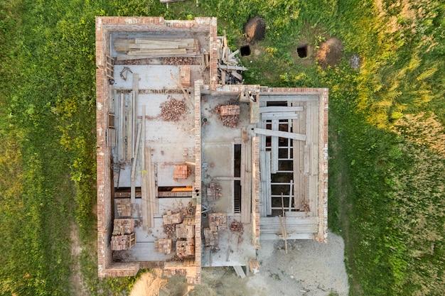 Vista aérea do canteiro de obras para a futura casa, piso do porão de tijolos e pilhas de tijolos para construção.