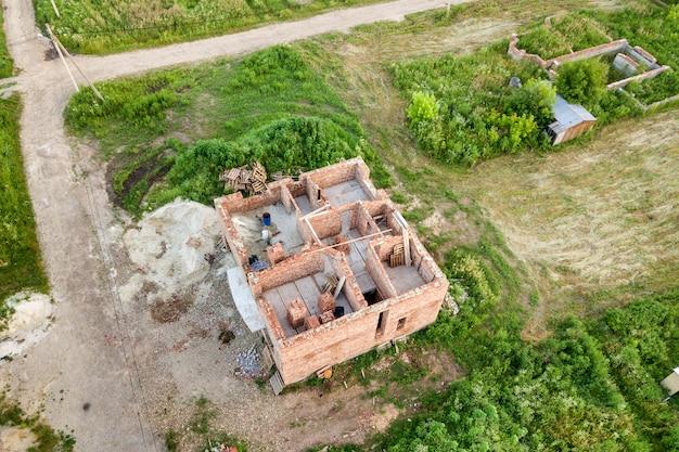 Vista aérea do canteiro de obras para futura casa, piso de porão de tijolo e pilhas de tijolos para construção.