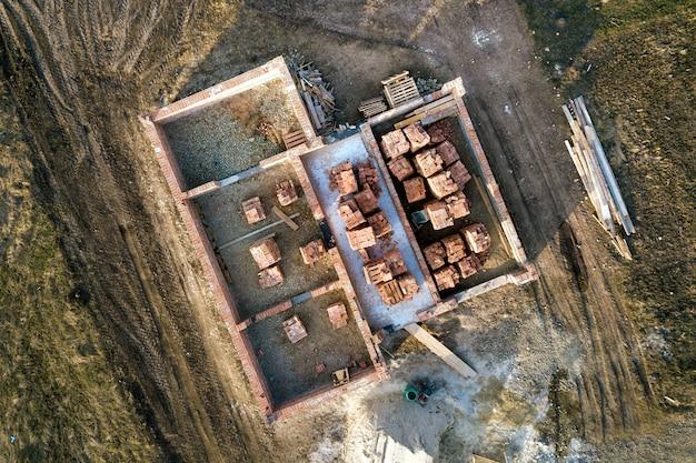 Vista aérea do canteiro de obras. trincheiras cavadas no chão e cheias de cimento como base para a futura casa, piso do porão de tijolos e pilhas de tijolos para construção.