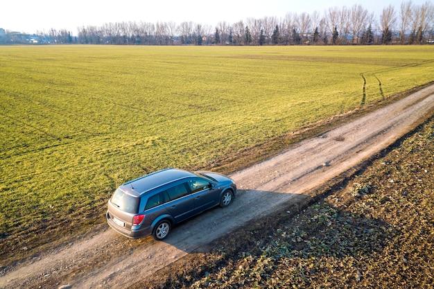 Vista aérea do carro dirigindo pela estrada de chão reto através de verde