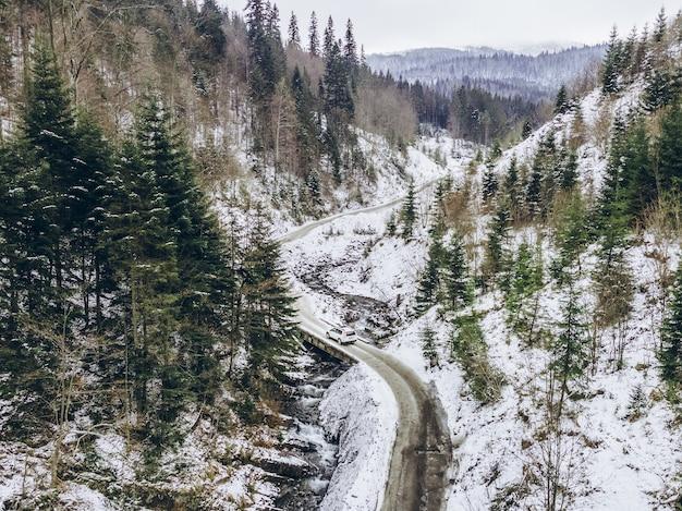 Vista aérea do carro se movendo pelo desfiladeiro no espaço da cópia de inverno nevado