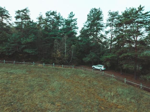 Vista aérea do carro suv perto da cerca da fazenda