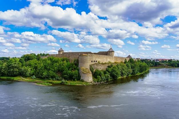Vista aérea do castelo junto à foz do rio junto à fronteira. narva, estônia.
