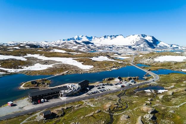 Vista aérea do centro de esqui à beira do lago cercado por uma paisagem montanhosa acidentada na noruega
