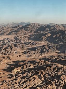 Vista aérea do deserto com colinas rochosas e montanhas.