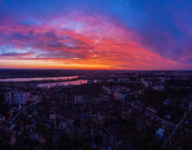 Vista aérea do dramático céu do sol acima da cidade ao entardecer.