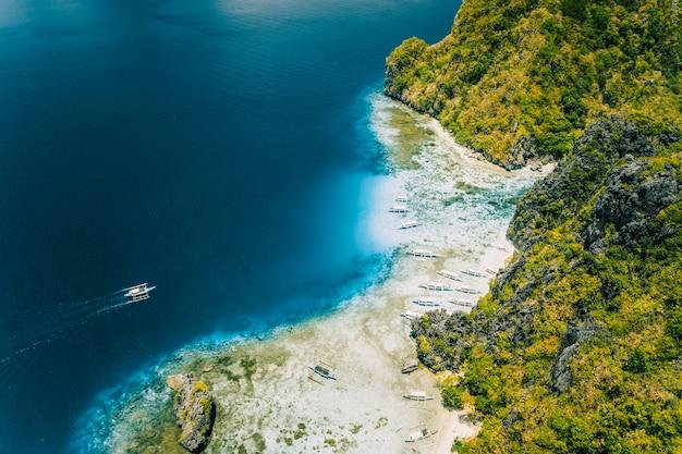 Vista aérea do drone da ilha tropical de shimizu. rochas costeiras de calcário, praia de areia branca em águas azuis. el nido, palawan, filipinas.