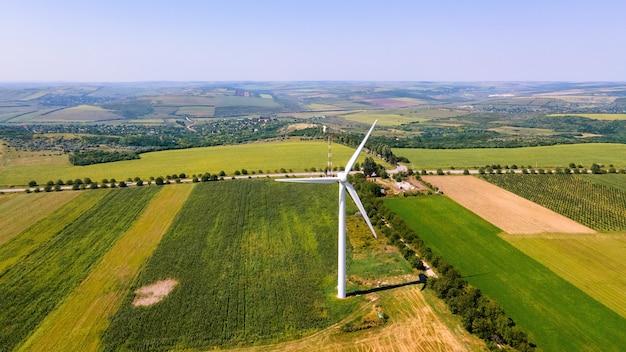 Vista aérea do drone da turbina eólica em funcionamento na moldávia campos extensos ao redor da vila