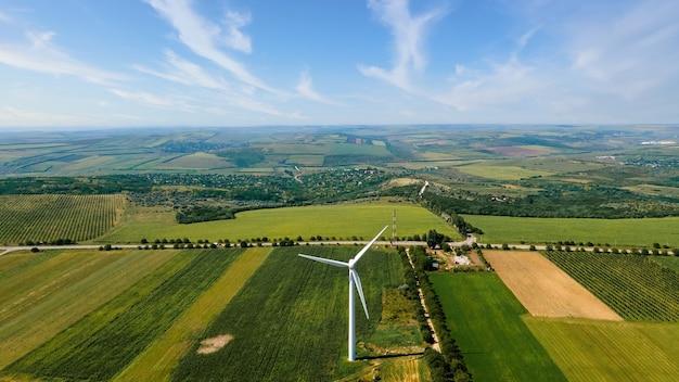 Vista aérea do drone da turbina eólica em funcionamento na moldávia. campos extensos ao redor da vila