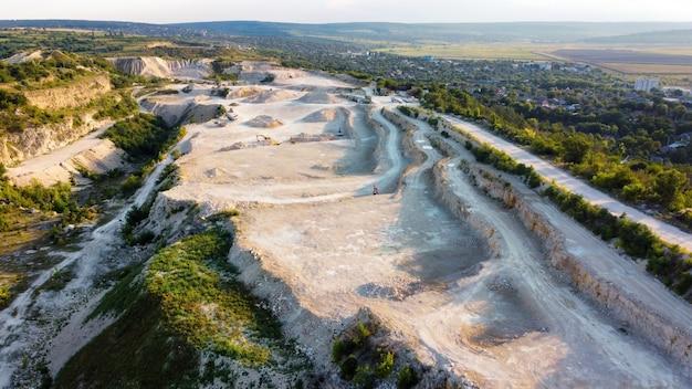 Vista aérea do drone das obras em uma pedreira de calcário na moldávia. campos e colinas ao redor, vila