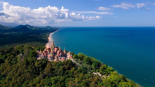 Vista aérea do drone de ângulo superior do templo wat pramahathadchedi pakdeeprakad ou tang sai na floresta montanhosa perto da praia do mar azul, destino de viagem em bang saphan, prachuap khirikhan, tailândia