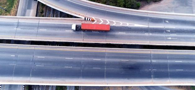 Vista aérea do drone de carga branca caminhão na estrada da rodovia com contêiner verde, conceito de transporte, importação, exportação logística industrial transporte transporte terrestre na via expressa de asfalto
